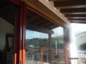 Custom painted and made Mahogany brown/brick retractable screen doors installed on the outside of the front view bi-folding doors for quick ventilation